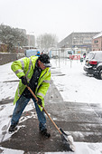 council-worker-clears-icy-paths-in-snow-