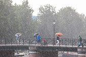 Amsterdam bridge. Sudden torrential summer rain. People on a bridge with umbrellas. One local in rain gear with shopping bag. - Stock Image