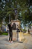 Jen Reid takes a photo of her black resin and steel statue titled A Surge of Power (Jen Reid) 2020, by Marc Quinn, where it is installed on the vacant Edward Colston plinth in Bristol city centre. - Stock Image