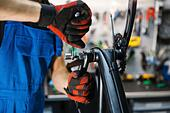Bicycle assembly in workshop, man installs crank - Stock Image