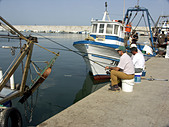 Three Anglers Fishing with Rod and Line next to a Commercial Fishing Boat, Puerto Deportivo de Fuengirola, Fuengirola, Andalucia, Spain