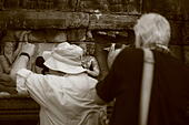 two-men-taking-photos-of-stone-carvings-