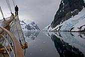 Sailing ship with man on bowsprit looking into the Lemaire Channel / Kodak Gap, Antarctica - Stock Image
