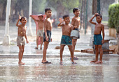 Boys waving and playing in pouring monsoon rain. Phnom Penh Cambodia - Stock Image