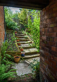 An old back yard garden with stone steps. - Stock Image