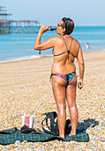 Summer concept. Summer drink. Very tanned woman in bikini having a drink on the beach on a hot Summers day in Brighton, East Sussex, England, UK. - Stock Image
