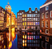 Amsterdam canals at night near red light district. St Nicolaaskerk Basilica of Saint Nicholas; Zeedijk and Oudezijds - Stock Image