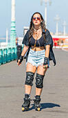 Young woman dressed for summer roller blading along the seafront promenade while listening to music, on a hot sunny day. - Stock Image