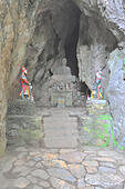 View of shrine in cave with statue of Shakyamuni Buddha in lotus position. Linh Ung Non Nuoc Pagoda. Da Nang. VIETNAM - Stock Image
