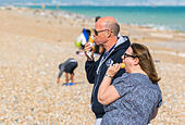 A couple eating ice cream on the beach in Summer in the UK. - Stock Image