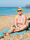 Pretty young blonde woman posing for a photo while sitting on a shingle beach on a hot day in Summer. - Stock Image