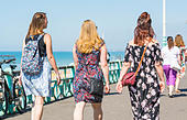 Females friends walking along the seafront promenmade dressed for Summer on a hot sunny Summers day. - Stock Image