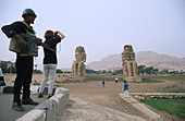 Tourists take snapshots under close guard of an Egyptian soldier at the Collossi of Memnon - Stock Image