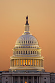 Dome and west front columns of the US Capitol building in Washington DC at dawn in warm early morning light. View from The Mall. - Stock Image