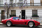Red Corvette vintage sports car parked outside a home in Knightbridge. Wealth in West London, UK. - Stock Image