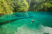 Young woman hanging on a rope over Blue Hole, Espiritu Santo, Vanuatu - Stock Image