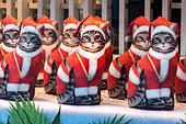 A row of identical Cats dressed as Santa in a shop window. - Stock Image