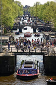 Amsterdam Canals. Four bridges with many cyclists on the Prinsengracht canal with canal tour boats and small pleasure - Stock Image