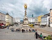 LInz Main Square Hauptplatz with Plague Column Pestsäule or Dreifaltigkeitssäule Holy Trinity Column. Linz Austria - Stock Image