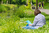 Woman sitting on grass by a stream in the UK countryside in Summer. - Stock Image