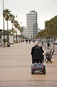 senior-man-in-motorized-wheelchair-on-th