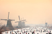 Dutch ice skaters in front of five of the 19 windmills at Kinderdijk in the Alblasserwaard polder, Holland, The - Stock Image