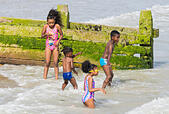 Black children at the seaside. A family of young black children playing in the sea in Summer in the UK. - Stock Image